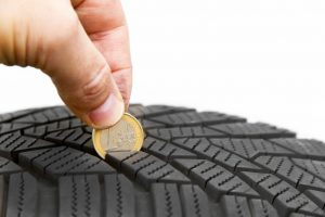 checking tyre with coin